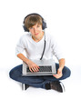 Boy wearing headphones sitting with a laptop