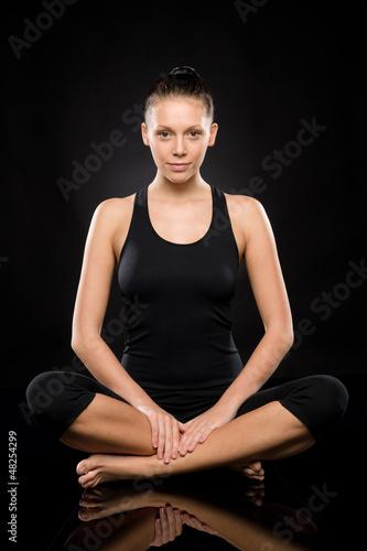 Young Caucasian woman doing yoga legs crossed