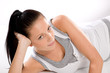 Woman lying in sportswear on white background