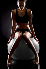 Young Caucasian woman exercising on fitness ball
