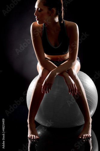 Young sporty woman relaxing on fitness ball