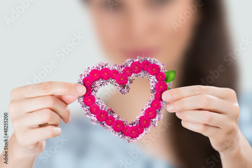 Young smiling woman holding red heart made of flowers. Focus on