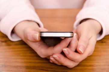 Hände einer Frau halten ein Smartphone