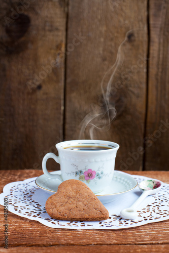 Heart shape Saint Valentine's Cookie and cup of coffee with stea
