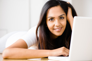 Beautiful Indian woman student using laptop computer at home
