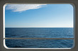 Ship window with a relaxing seascape and blue sky view.