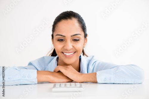 Happy Indian business woman using calculator