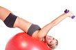 A fit woman doing a push up routine on a red exercise ball
