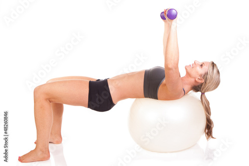 A fit woman doing a push up routine on a white exercise ball