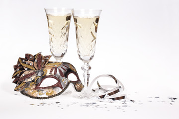 Masquerade mask and champagne isolated on white