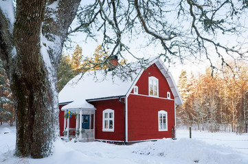 Rotes Holzhaus im winterlichen Schweden
