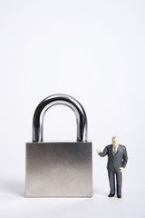 Businessman figurine standing next to padlock