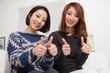 Two young Asian woman show thumb in home background.