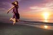 Girl jumping and dancing on beautiful beach.