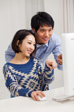 Young Asian couple using PC
