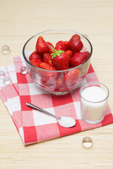 Fresh strawberries and sugar in glass bowls