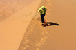 man running on sahara desert sand dunes