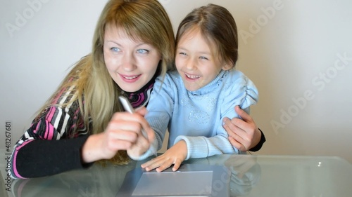 happy mother and daughter drawing on the graphics tablet