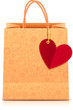 Ornate paper shopping bag with heart label on golden ribbon