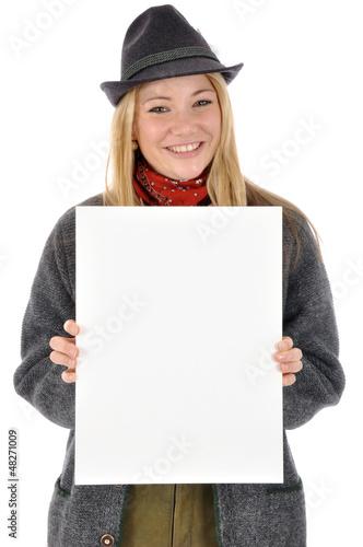 Junge Frau in bayrischer Kleidung hält leeres Schild