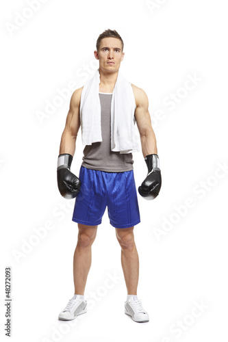 Young man in sports outfit wearing boxing gloves