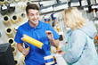 Seller demonstrating paint roller to buyer