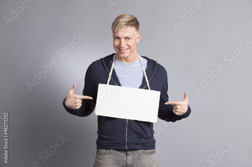 Joyous man pointing fingers at blank signboard.