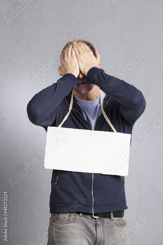 Frustrated sad man presenting blank signboard.