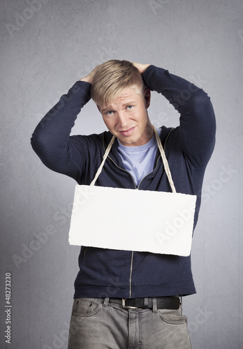 Devastated man showing white empty signboard.