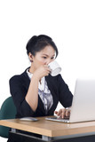 Young business woman yawning at her desk with a cup of coffee