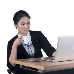 Business woman holding a cup of coffee and looking at laptop scr