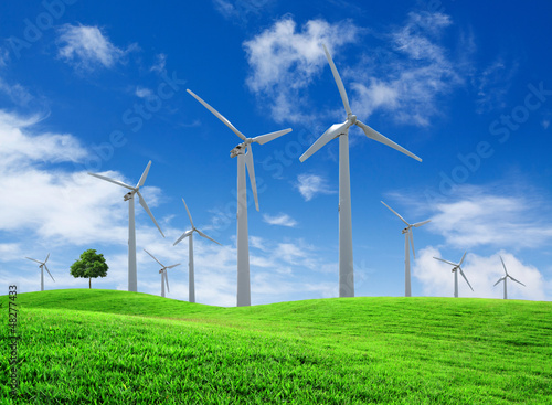 Wind turbines farm on green field landscape
