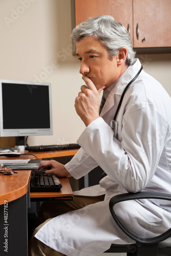 Pensive Doctor Sitting At Desk