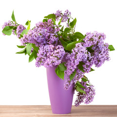 Bouquet of lilac flower in a jug on wooden surface