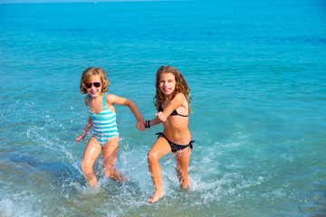 children girls friends running together in the beach shore