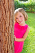 child happy girl smiling rear tree trunk in garden