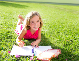 child kid girl doing homework smiling happy on grass