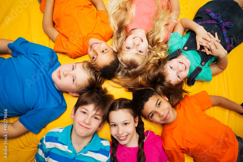 Group of happy kids laying in circle