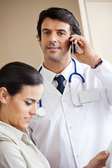 Doctor Answering Call While Standing With Colleague