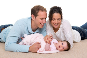 Baby mother and father happy family lying on carpet