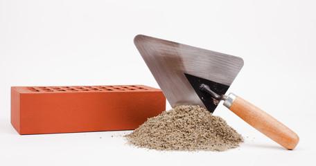pile of sand, brick and mason trowel