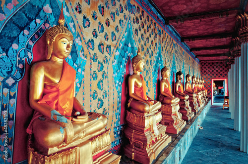 Wall mural golden statues of Buddha in Wat Arun temple, Bangkok