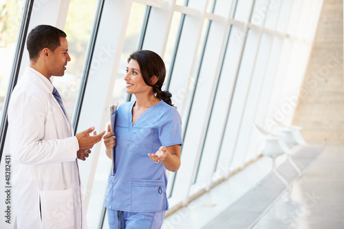 Medical Staff Having Discussion In Modern Hospital Corridor