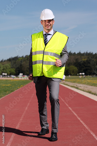 businessman with hard hat and yellow vest on track