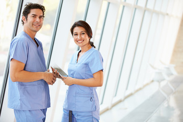 Medical Staff Talking In Hospital Corridor With Digital Tablet