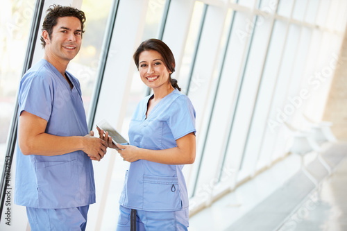 Medical Staff Talking In Hospital Corridor With Digital Tablet