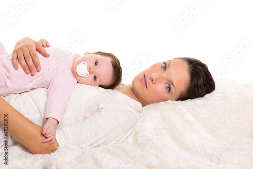 Baby girl and mother lying happy together on white fur