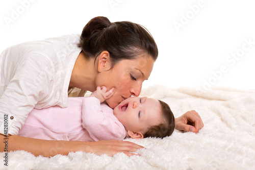 Baby girl and mother lying happy playing together