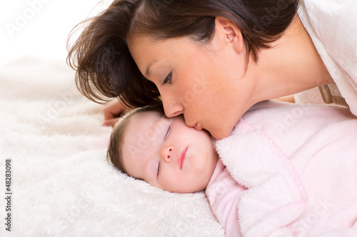 Baby girl and mother kissing her lying happy on white