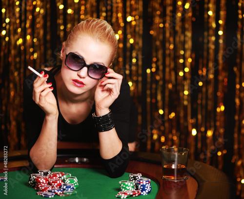 Frau mit Zigarette spielt Poker